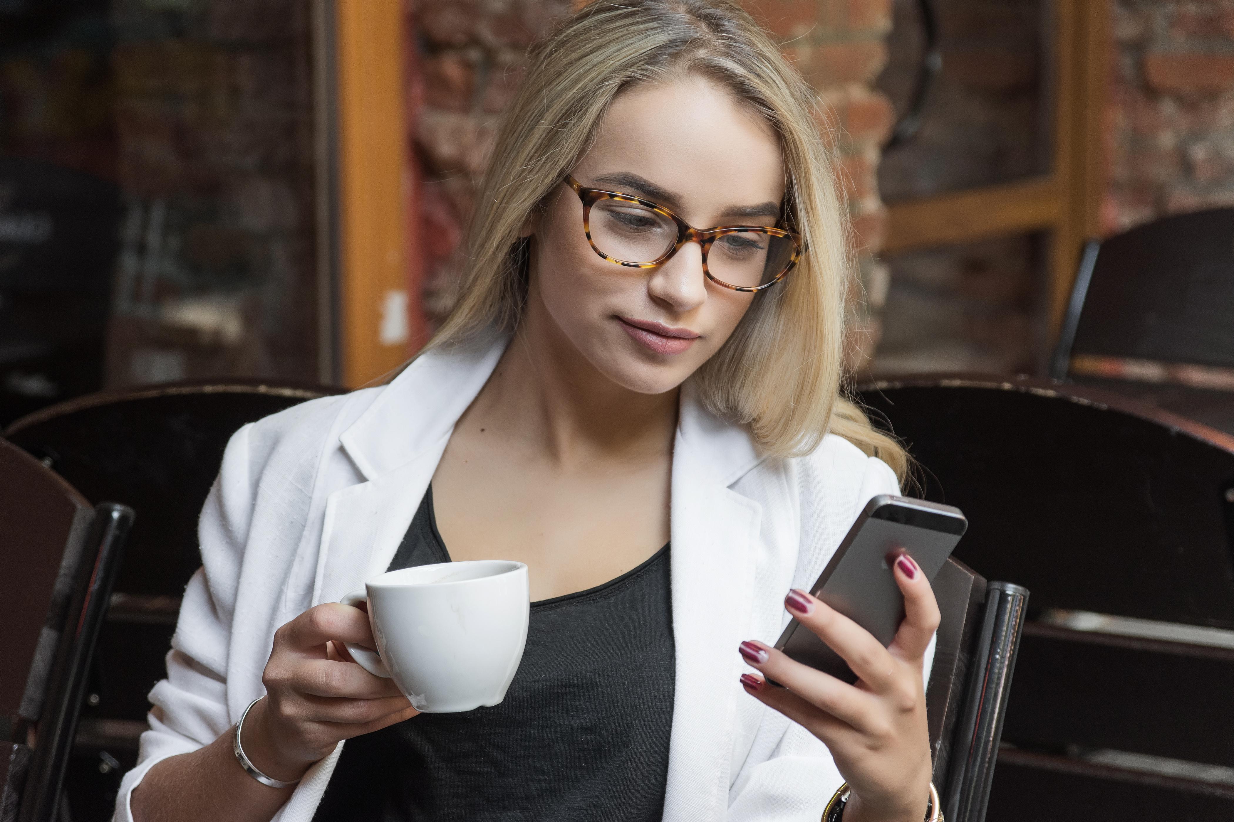 Junge_Frau-mit_Smartphone-Tasse-Straßen
