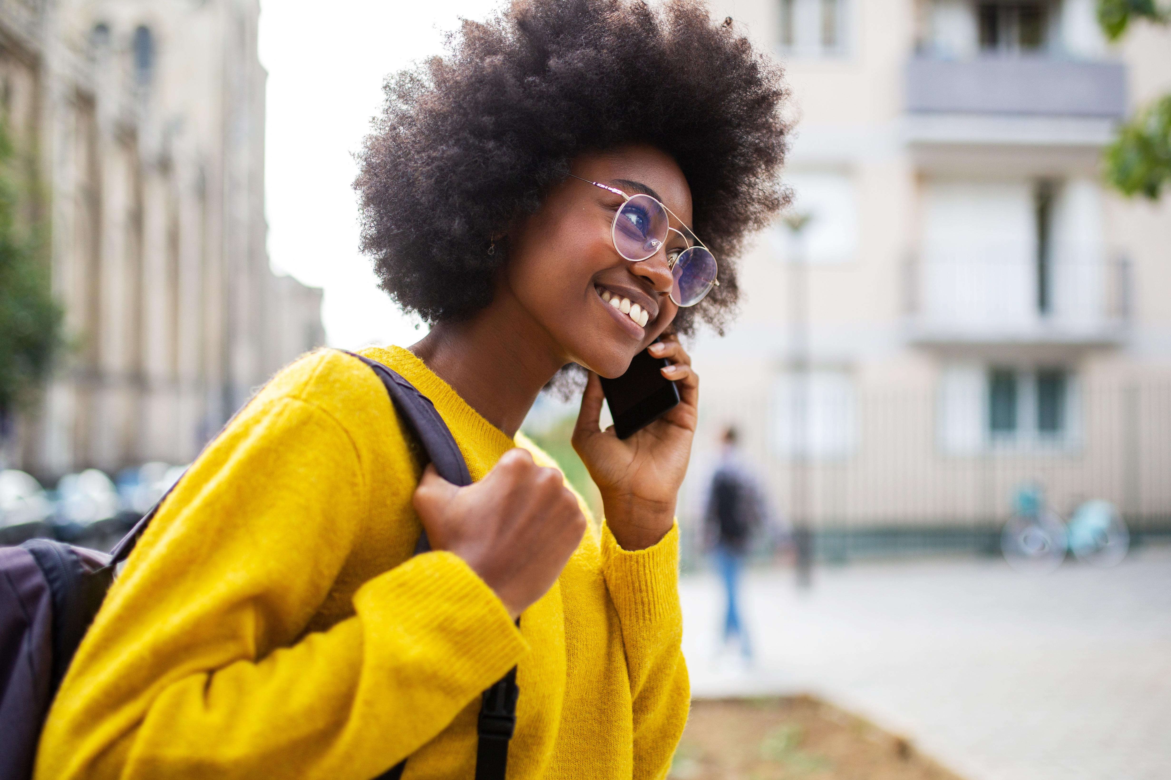 Junge Frau-mit Smartphone-Rucksack-gelbe