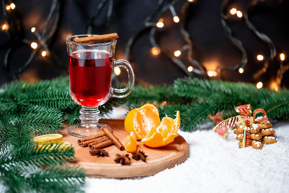 A glas of mulled wine with tangerines, cinnamon and christmastree branches on round cutting board