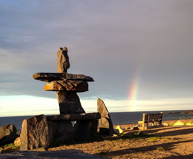 Stone statue and park bench overlooking the Hudson Bay and a rainbow in Churchill, Manitoba