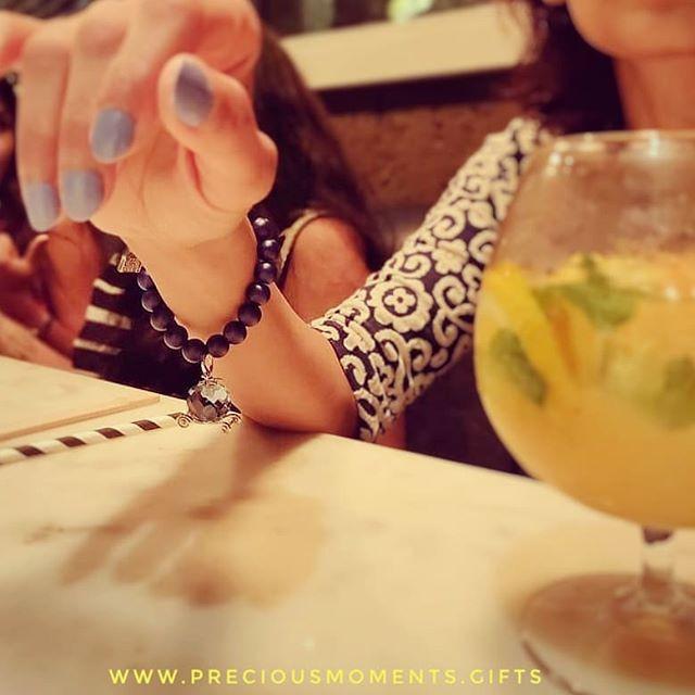 A woman wearing 14ct gold plated Disney Cinderella 'Pumpkin Carraige' bracelet at an evening dinner with friends
