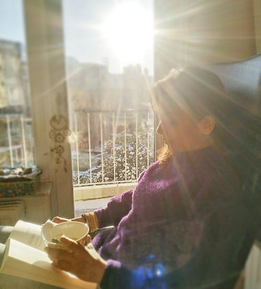 A woman reading a book with a mug of coffee in hand and sun rays falling through the glass door
