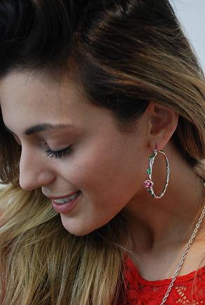 A happy woman wearing Disney Beauty & the Beast Rose Hoop Earrings