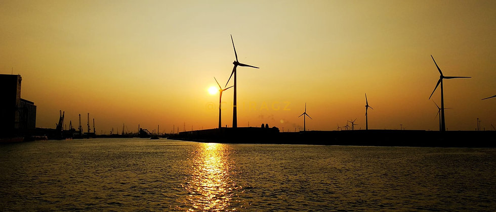 Windmills on the riverside in the evening sunset