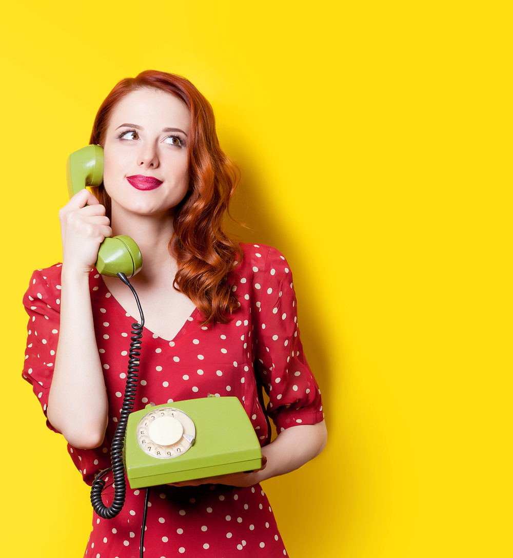 Woman in red holding rotary phone