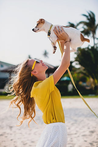 young-stylish-hipster-woman-holding-walking-and-playing-with-dog-in-tropical-park-smiling-