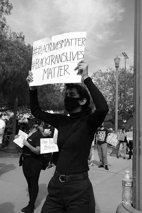 person stands with a sign that says blacklives matter. black translives matter