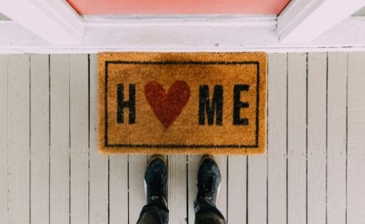 A door mat with the word home on it, by a front door, with someone standing near beside the mat, with only their shoes and ankles in the image