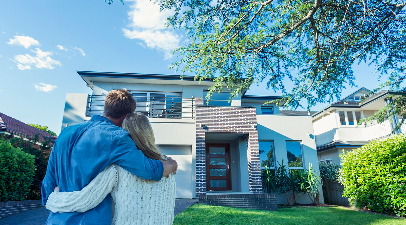 This image shows a couple looking at a house they are buying.