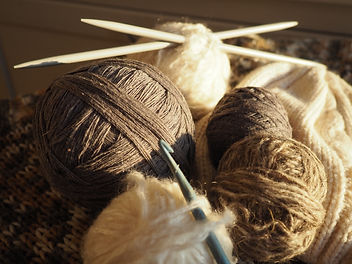 Balls of yarn, knitted clothes, knitting needles and crochet hooks. Knitting as a hobby. B