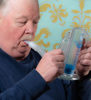 Elderly man using incentive spirometer f