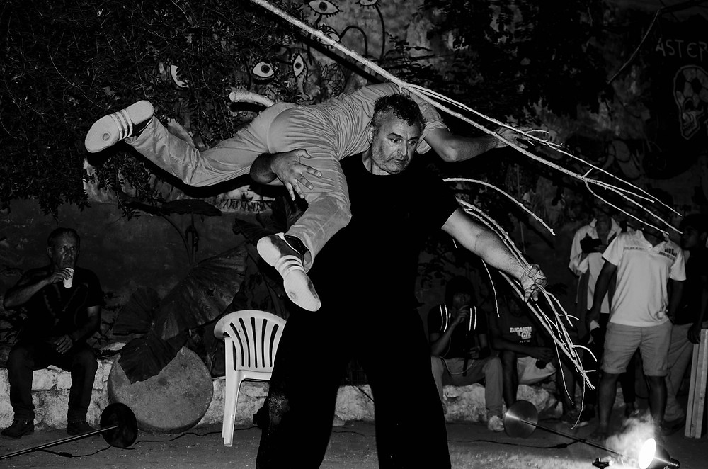 "Panagiotis Andronikidis of passTRESSpass lifting Abduol into a spin in a contact improvisation-inspired dance duet called ""roots"" performed in July 2016. Photo by Nadir Noori."