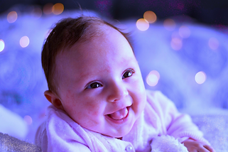 A smiling baby surrounded by fairy lights