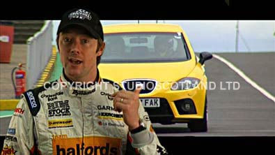 Film still showing racing driver with greenscreened  track car in background