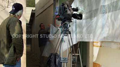 Camera, cameraman with poly sheeting to deal with the high contrast lighting.