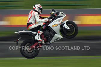 Tracking action with rider Niall Mackenzie poping a wheelie