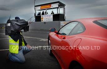 Cameraman preparing for fast track action with Farrari car.