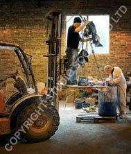 Forklift and tripod mounted camera shooting in industrial environment.