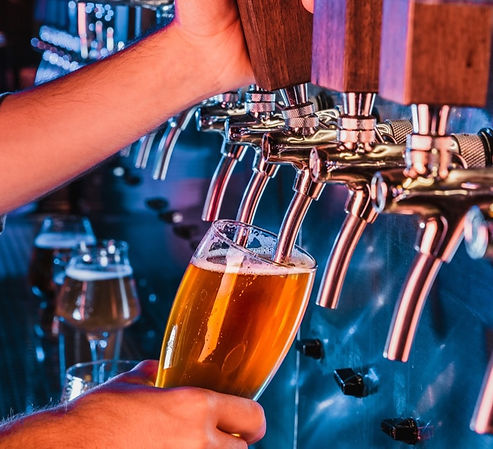 Hand-of-bartender-pouring-a-large-lager-