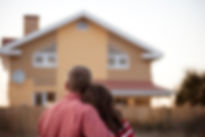 Homeowners couple embracing looking at new house.