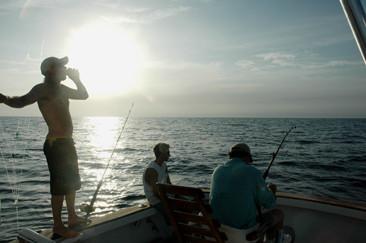 anglers fishing for swordfish near sunset