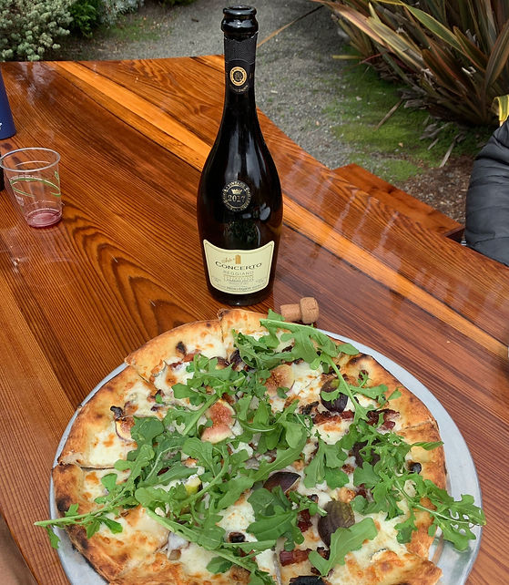 Fig pizza and a bottle of wine on a wooden table in the garden.