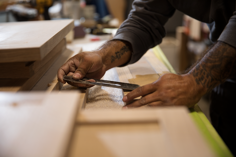 Detail photo of hands of MN Builders craftsman in millwork shop.