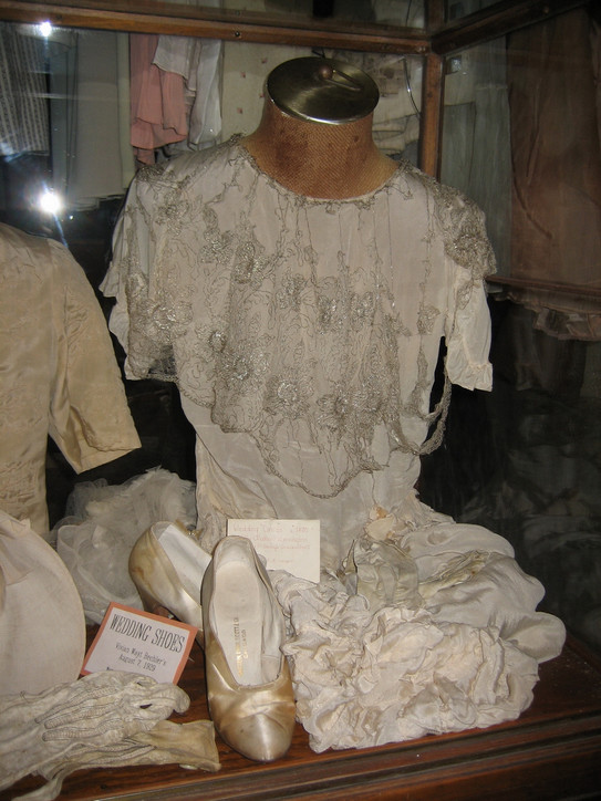 Wedding dress, shoes, and gloves of Vivian Louise Wayt Bechler, daughter of Leon R. and Mary Blaine Lamoreaux Wayt, in a showcase at the museum.