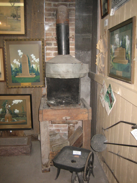 Photo of what is now known as 'Wayt Corner' in the basement of the museum. There are a number of artifacts from the old business stored here, including this wood burning stove. If you look closely on the wall next to the large painting on the right, you can see a cluster of old invoices from the company (closeup next slide).