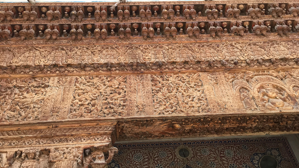 Teak beam with intricate carving.