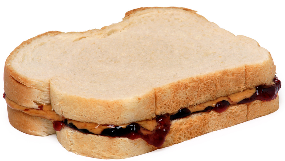 Peanut butter and jelly sandwich with grape jelly on white bread.