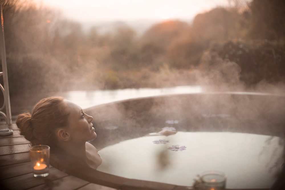 woman in hot tub outside with candles lit, relaxing