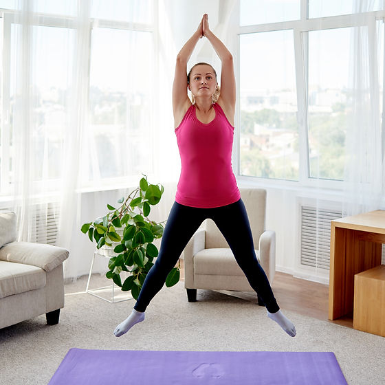 Young fitness woman doing jumping jacks