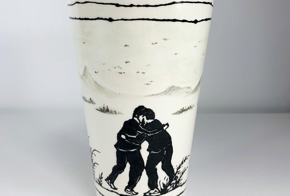 2 Men Hugging in a Landscape Mug/Vessel