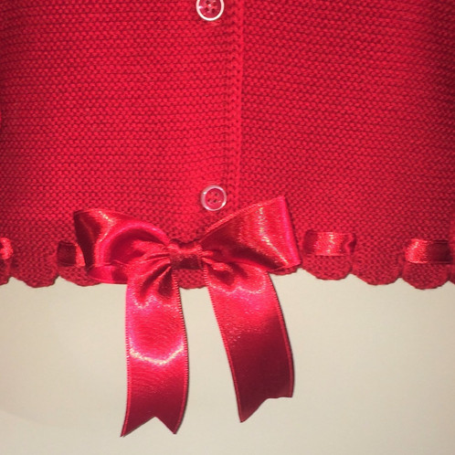 dff44fdd78796 A beautiful short bolero cardigan by Couche tot. This long sleeve bolero  has a threaded satin ribbon through the waist and cuffs with a large satin  bow on ...