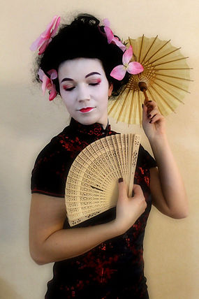 Authentic Geisha makeup look, with umbrella and fan, flowers in hair, white face, red lips and eye shadows