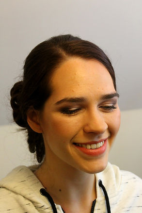 Brunette trying her bridal makeup look, with orangey lips and classic bridal eye makeup