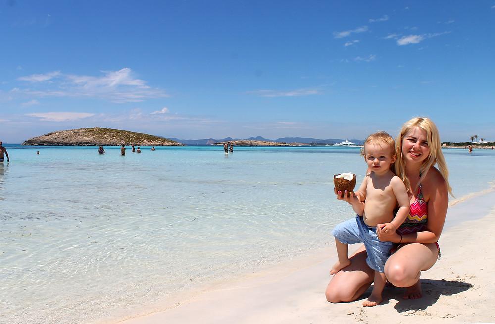 Drinking fresh coconut juice on beach in Formantera, Spain