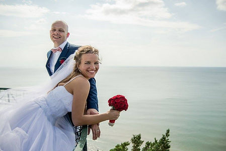 Bride and Groom during their wedding photo shoot, red accent, clasic makeup by the sea