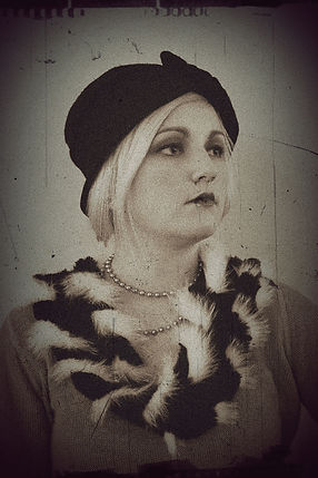 20's style makeup and outfit, with pearls and boa. Sad dark eyes, black and white photo