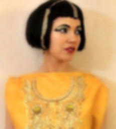 Cleopatra makeup, bold eyeliner, gold in hair and outfit, black eyebrows