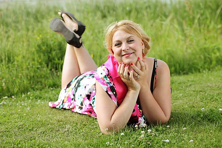 Blonde girl laying in the grass during her hens night with professional makeup, red nails and flower print dress