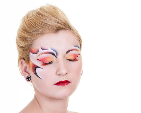 red, yellow, orange eye makeup, red lips, with interesting design on face