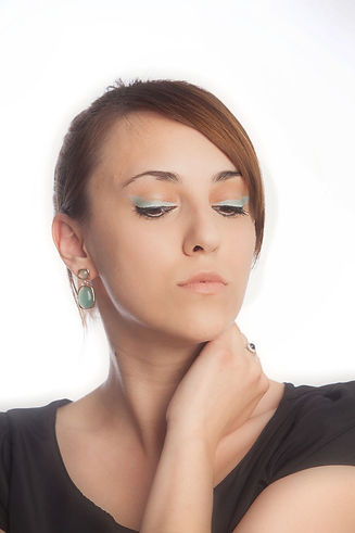 Double winged eyeliner, green and black, pale nude lip, green earings