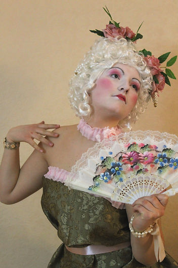 Baroque style white wig, makeup look, white face, bright red cheeks, red small lips, high eyebrows, flowers, chique dress