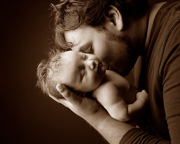 Father kissing his newborn