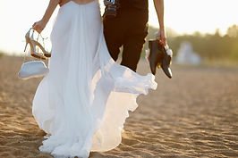 The lower half of a bride and groom on their wedding day carrying their shoes as they walk on a sandy beach near Cardiff, South Wales