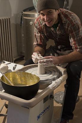 henry Carrelet tournant une petite bouteille en grès blanc dans l'Atelier Dipneuste