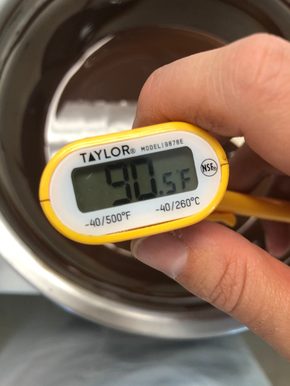 Thermometer stuck in a  of dark chocolate