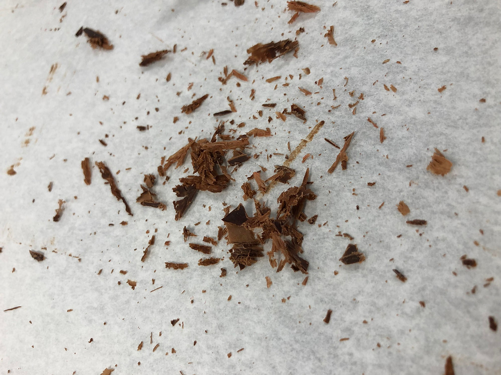 Tiny shavings of dark chocolate on a parchment paper